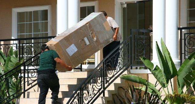 Men Carrying a Big Box Up Stairway